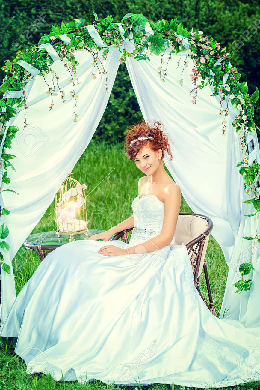 Beautiful Bride With Chaming Red Hair Sitting Under The Wedding Arch Dress And Accessories: Wedding Dress With Red Accesories At Websimilar.org