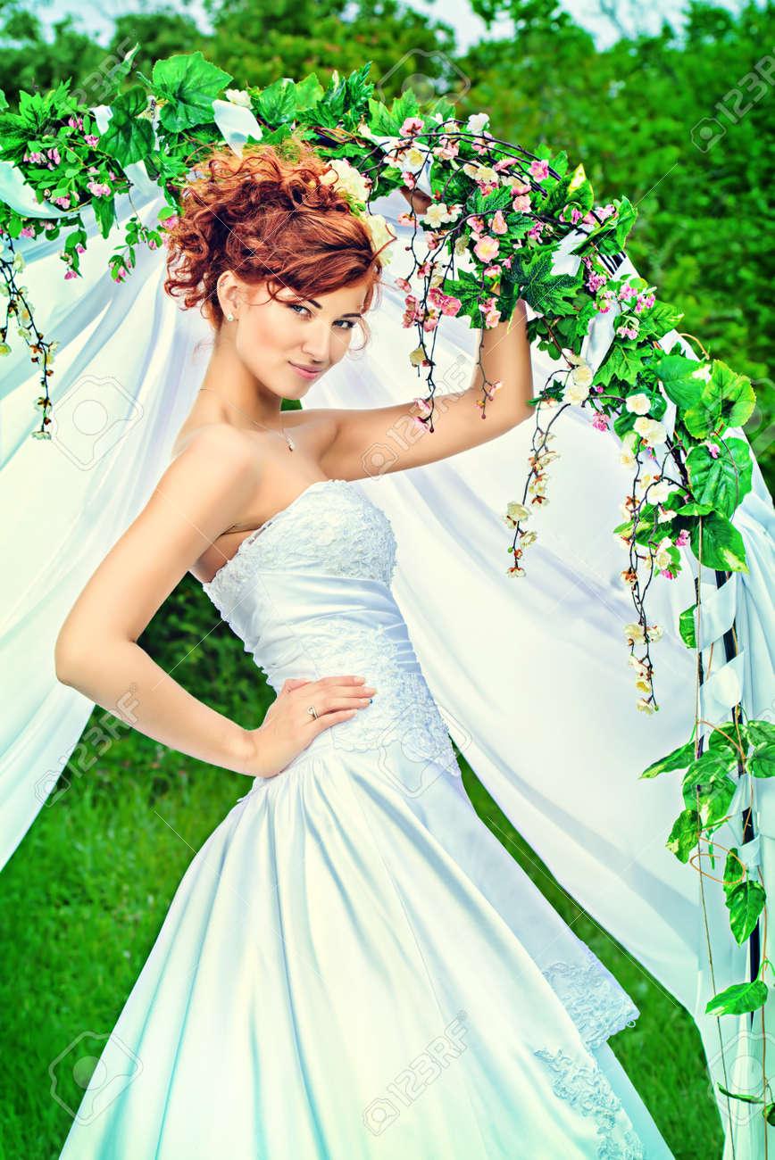 Schone Braut Mit Chaming Roten Haaren Steht Unter Dem Hochzeitsbogen