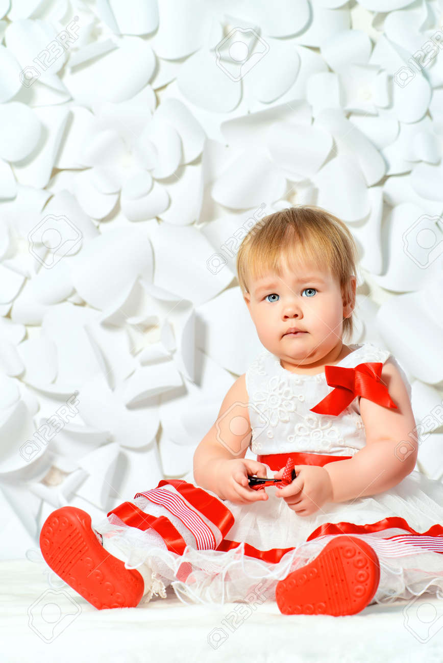 cute baby girl in a beautiful dress on a background of white.. stock