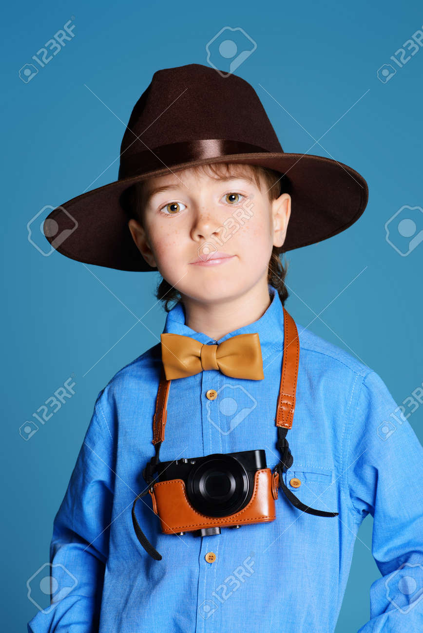 portrait of a cute 7 year old boy in elegant hat and bow tie stock