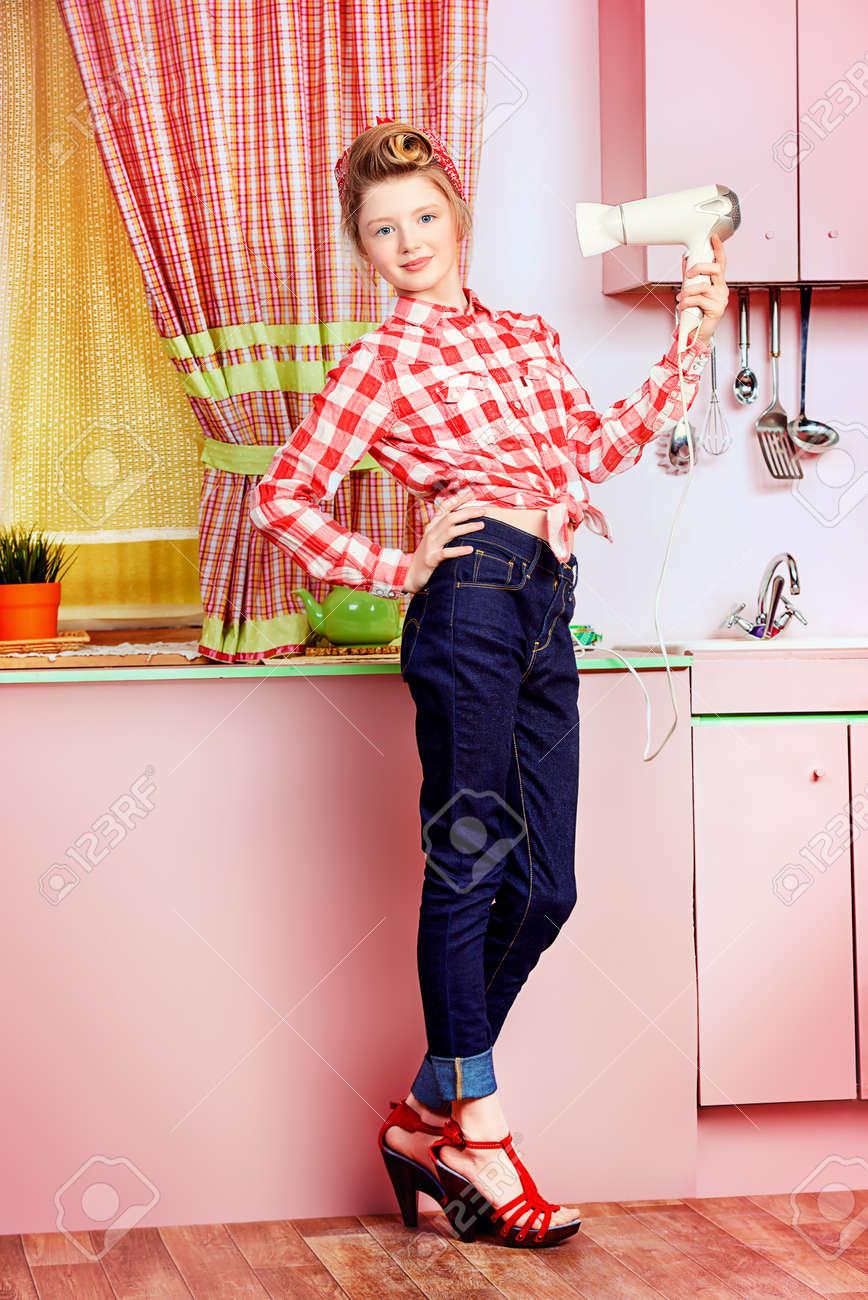 640d278f9b28cb Pretty pin-up girl tiener stijlen haar haar met een föhn op een roze keuken