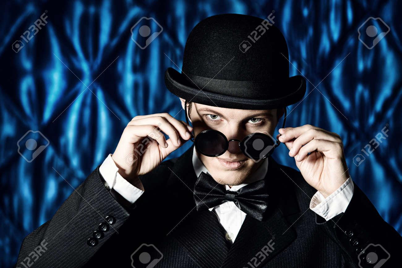 d84bfa0d914 Portrait of an elegant old-fashioned artist man wearing black suit and  bowler-hat