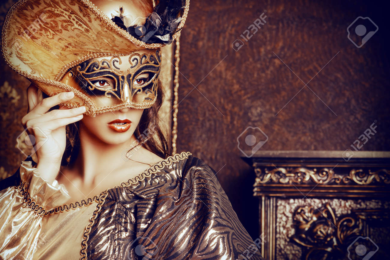 Venetian masquerade carnival. Elegant lady wearing beautiful lush dress and venetian mask stands in a palace room. Renaissance. Barocco. Fashion. - 43156028