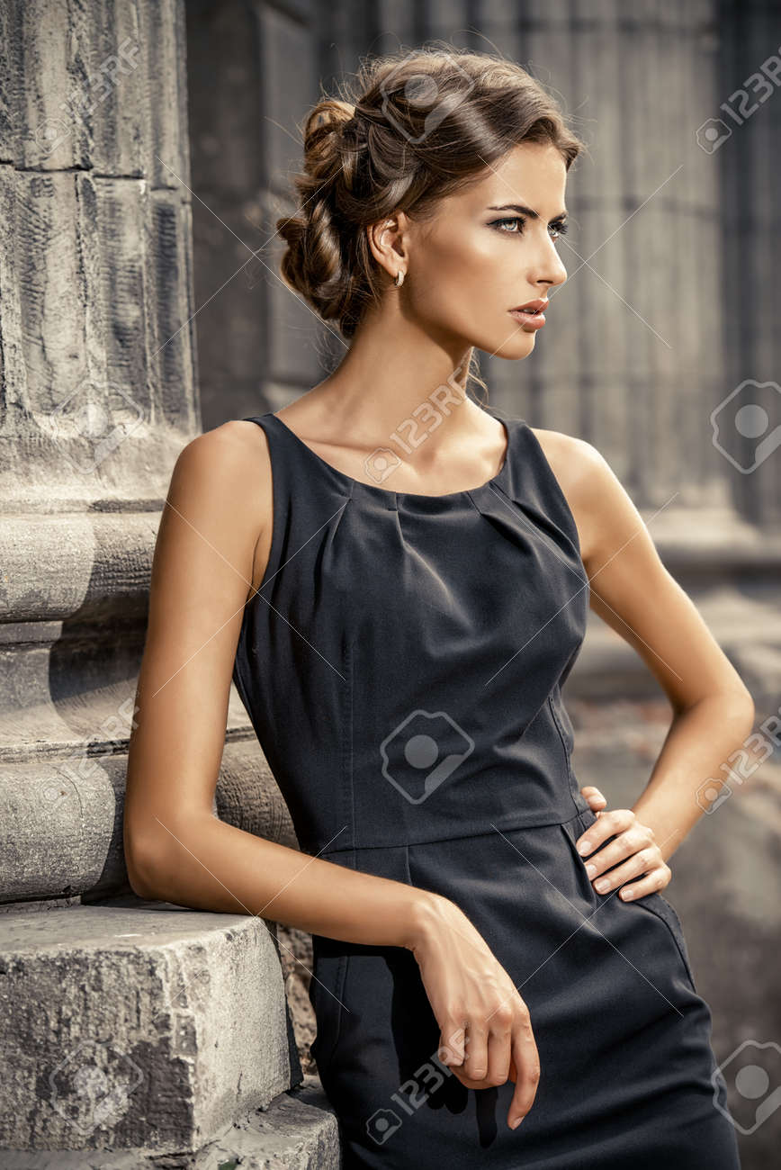 Vogue model wearing black dress posing over urban background. Fashion shot. Stock Photo - 43832893