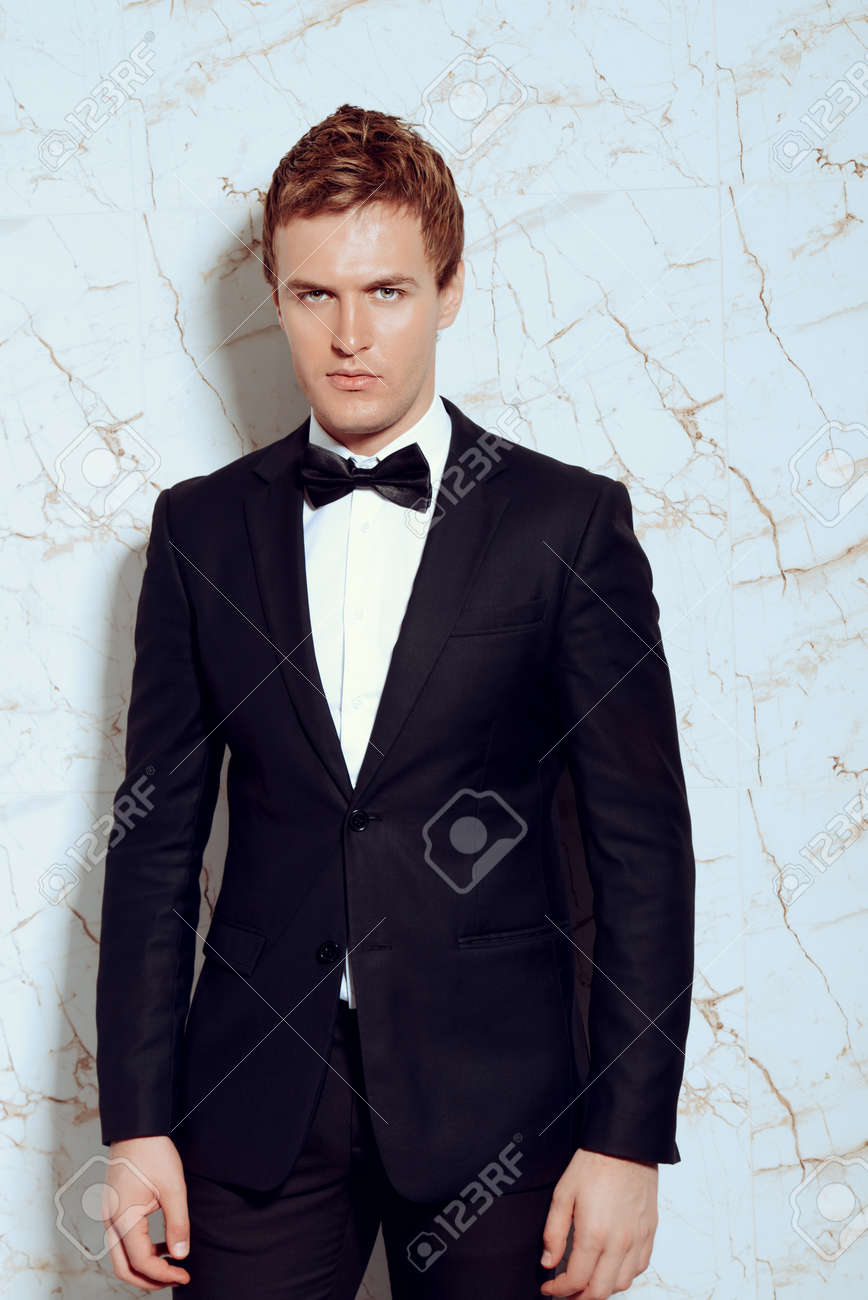 cbd9ca8929889 Stock Photo - Vogue shot of a handsome man in black suit and bow-tie. Men s  beauty