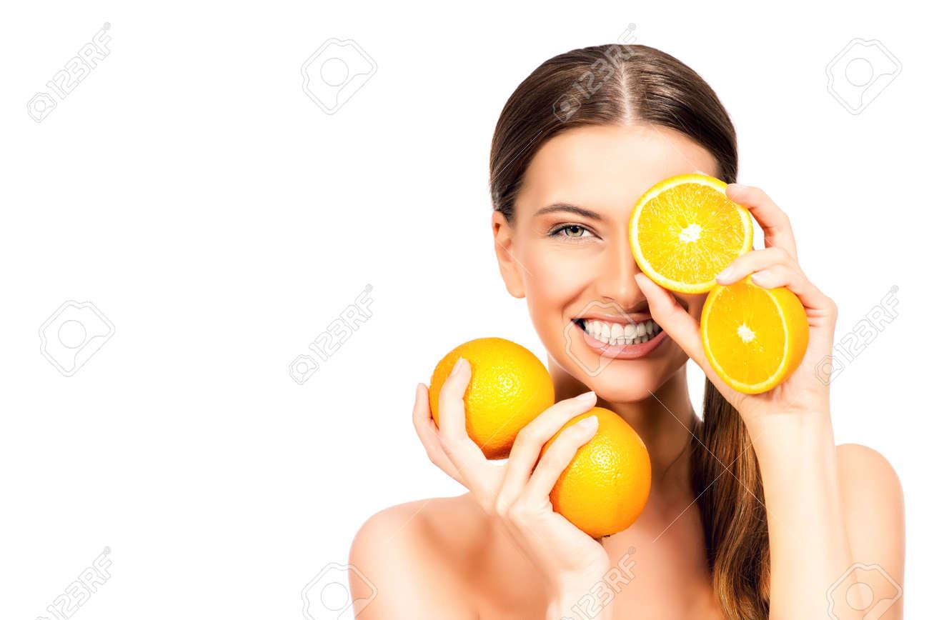 Joyful young woman holding juicy oranges before her eyes Stock Photo - 43906352