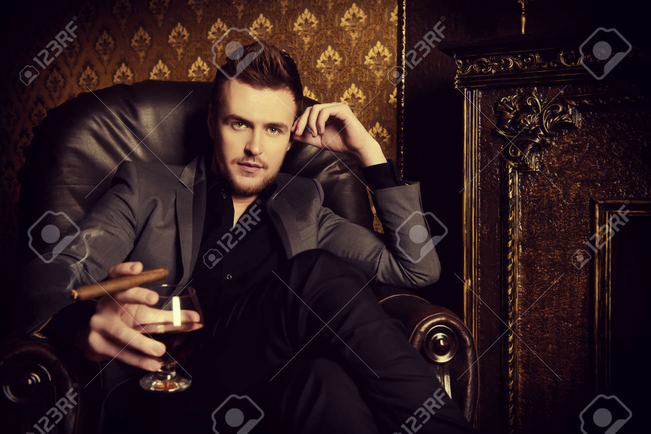 Elegant man in a suit with glass of beverage and cigar in vintage room Stock Photo - 43906219