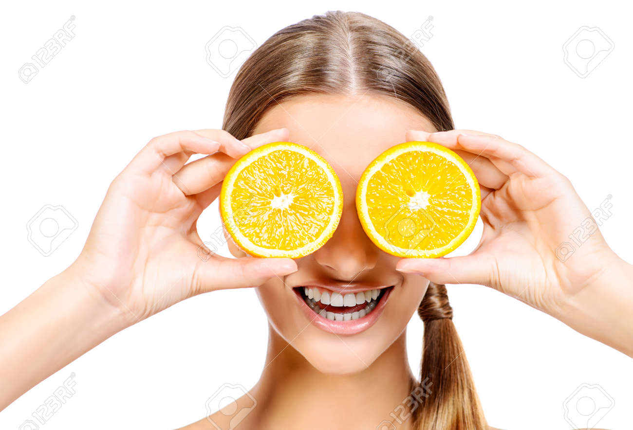 Joyful young woman holding juicy oranges before her eyes. Healthy eating concept. Diet. Isolated over white. Stock Photo - 44127447