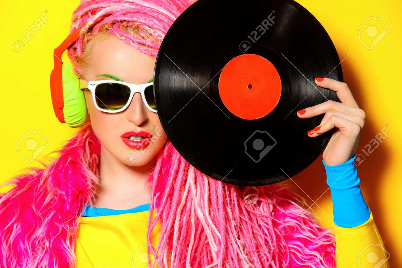 Glamorous modern DJ girl posing with vinyl record. Disco, party. Bright fashion. Stock Photo - 44512867