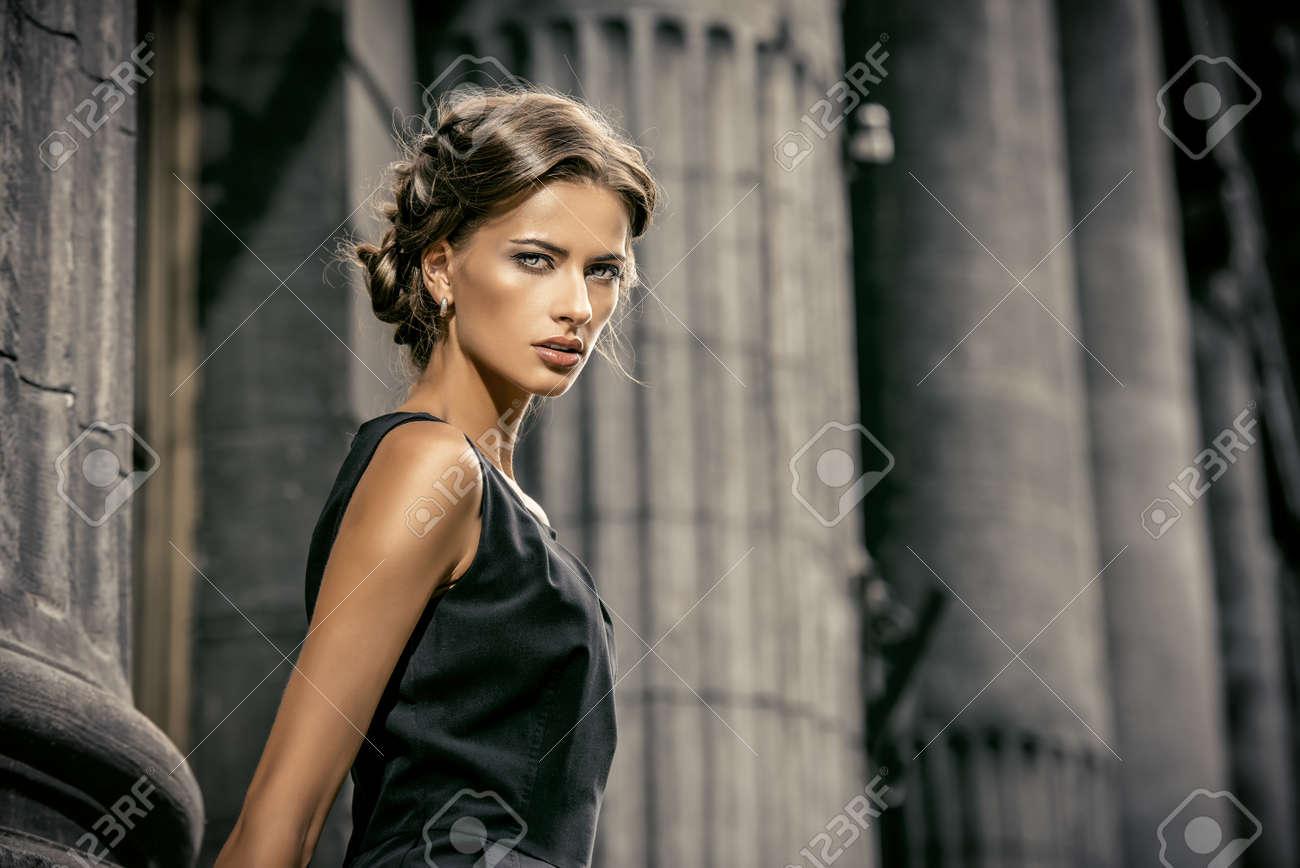 Vogue model wearing black dress posing over urban background. Fashion shot. Stock Photo - 44513291