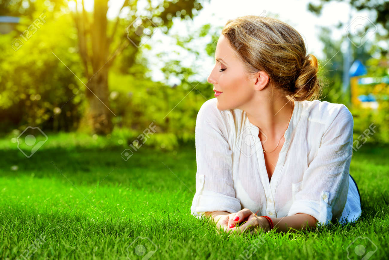 Beautiful smiling woman lying on a grass outdoor. She is absolutely happy. Stock Photo - 44903538