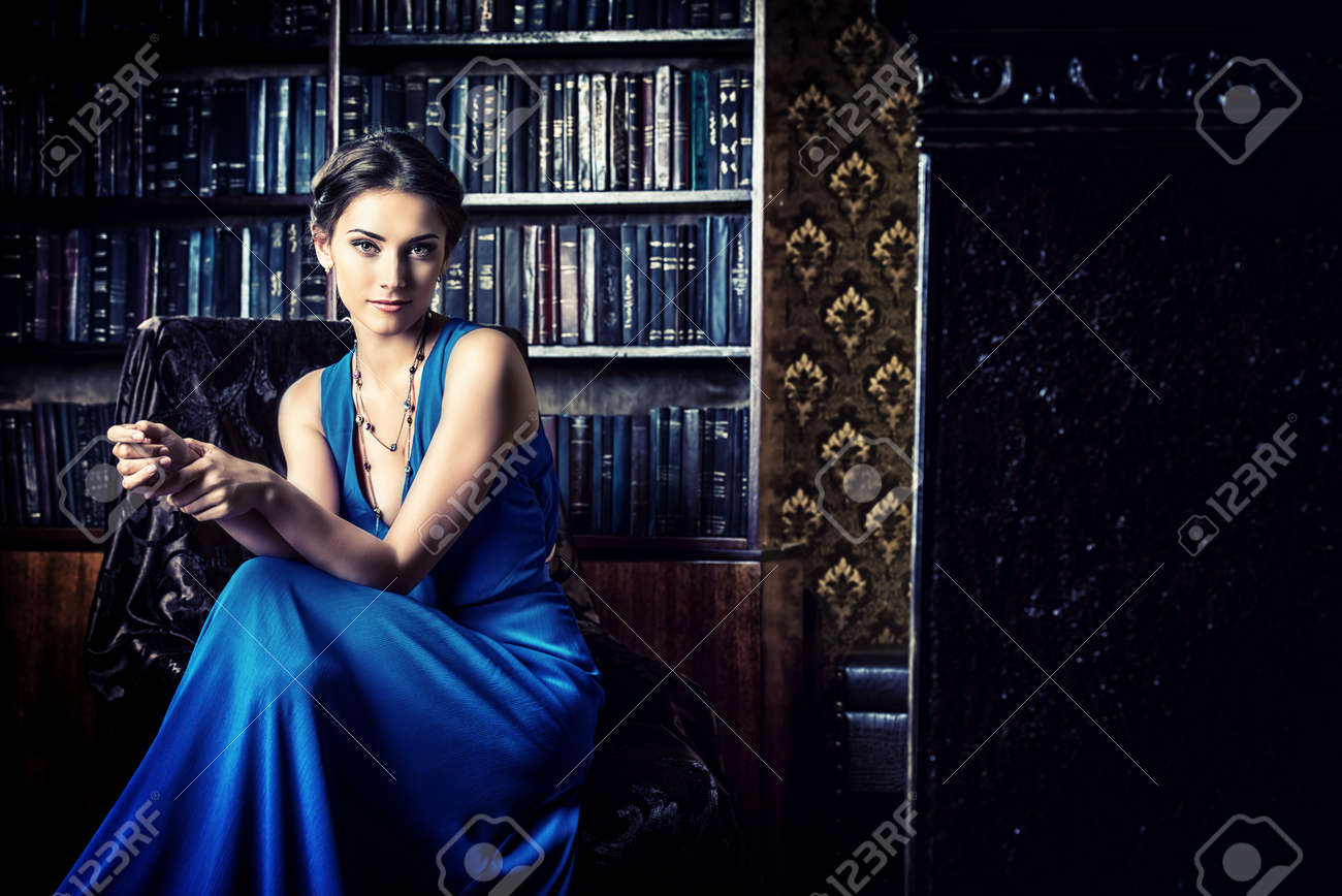 Elegant lady wearing evening dress sitting in the chair in the old vintage library Stock Photo - 45031260
