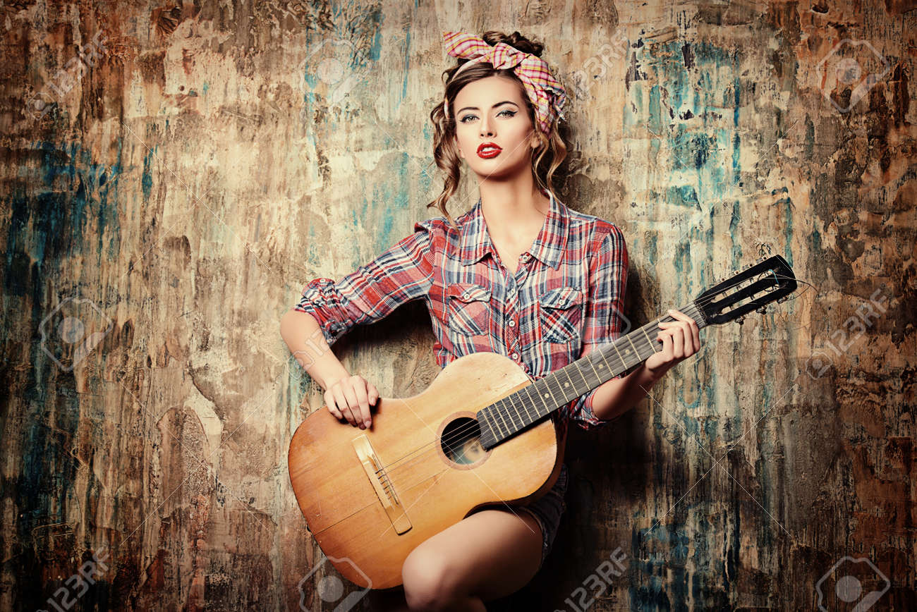 Pretty pin-up girl posing with guitar Stock Photo - 45250437