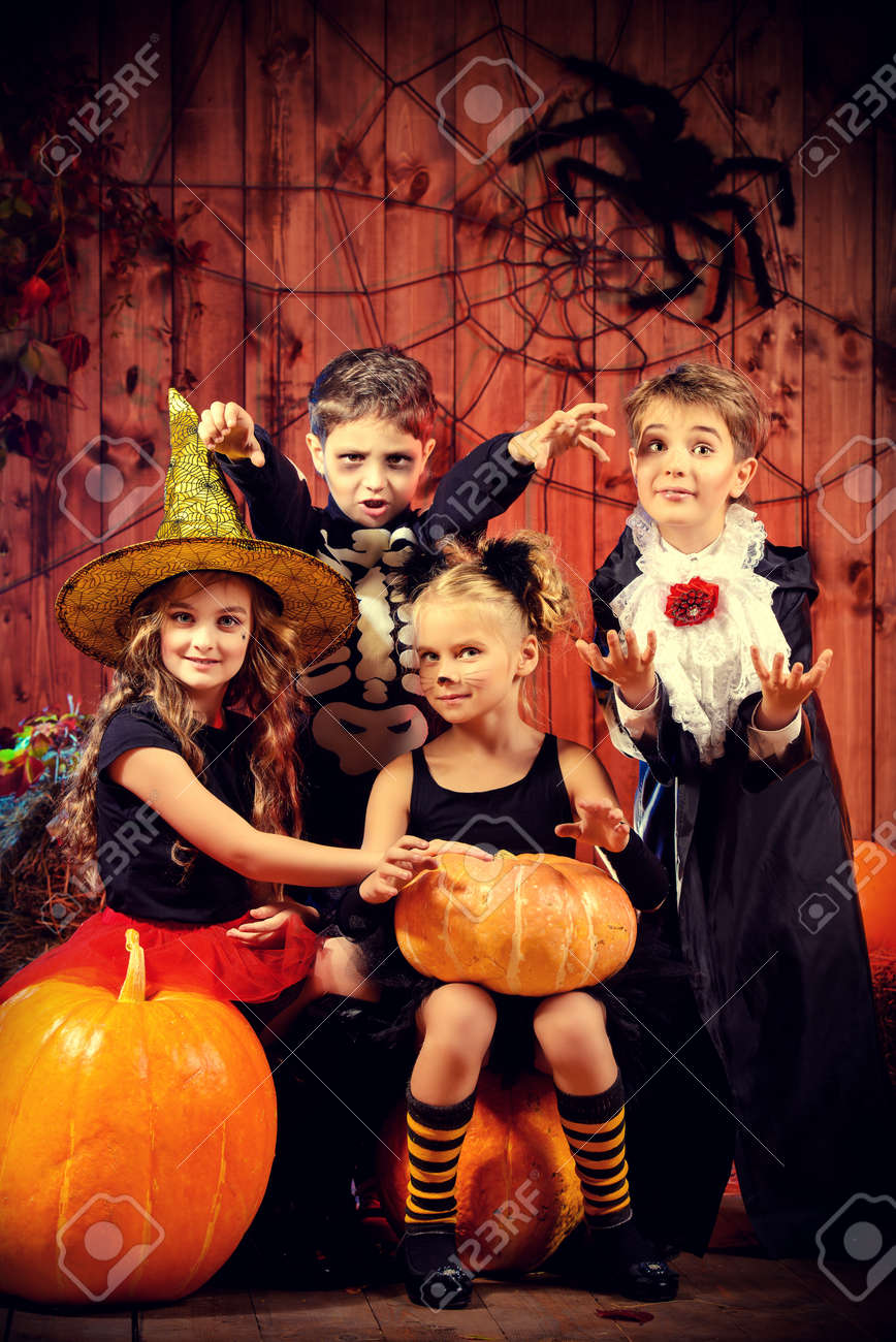Cheerful children in halloween costumes celebrating halloween in a wooden barn with pumpkins. Halloween concept. Stock Photo - 45948833
