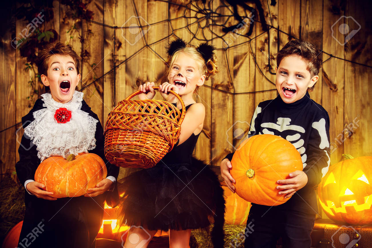 Group of joyful children in halloween costumes posing together in a wooden barn with pumpkins. Halloween concept. Stock Photo - 45948877