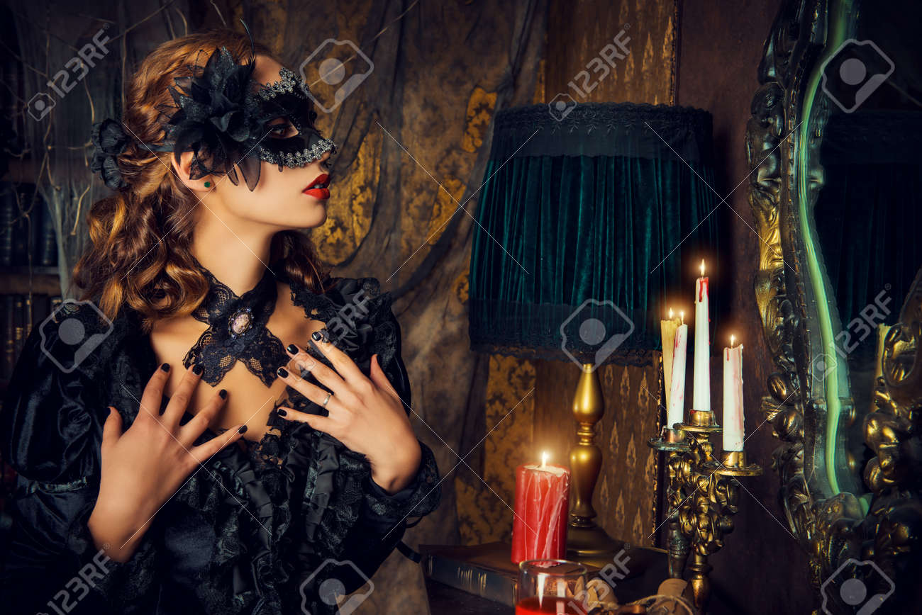 Charming mysterious girl in black mask and black medieval dress stands in a castle living room. Vampire. Halloween concept. Vintage style. Stock Photo - 45949982