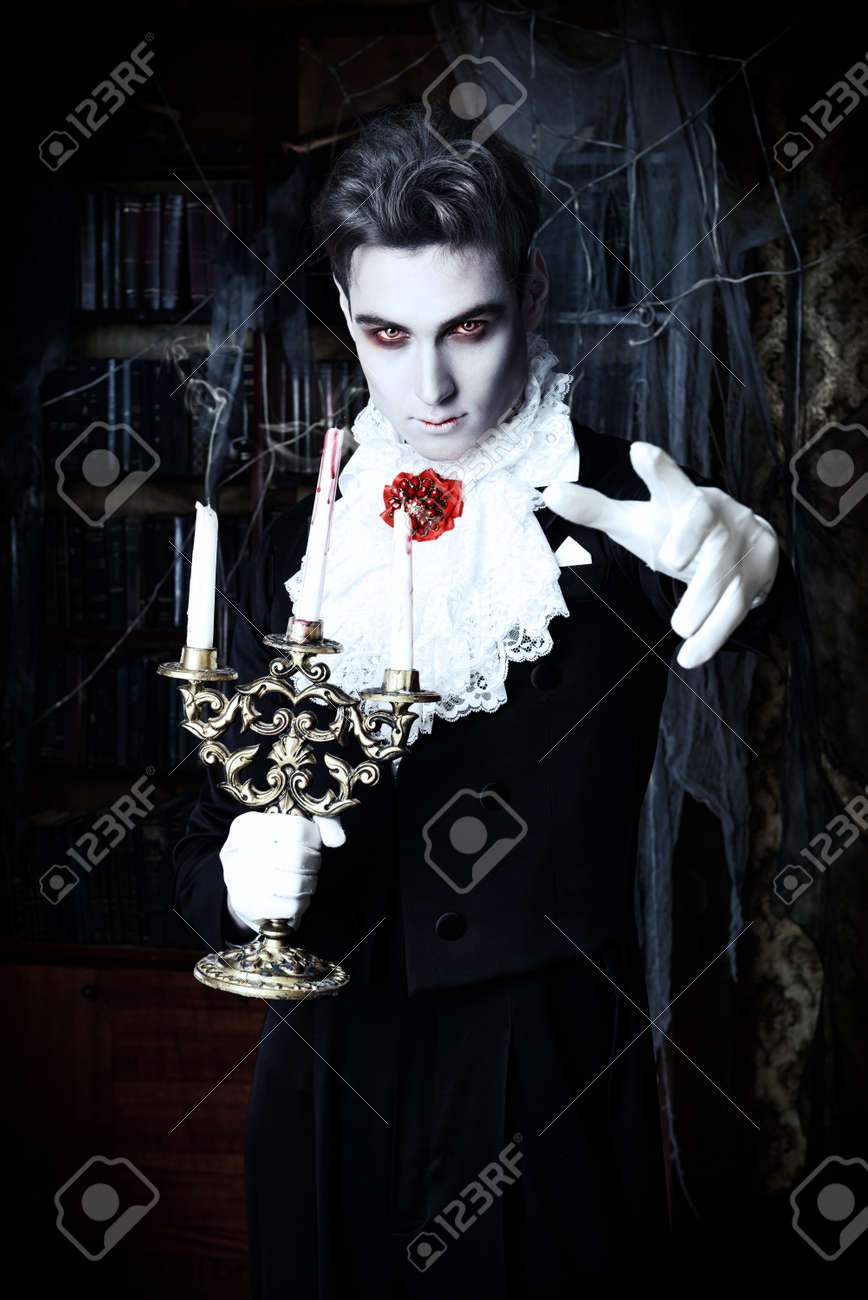 Handsome Vampire Man Wearing Elegant Tailcoat Stands In The Old Medieval Castle Halloween Stock