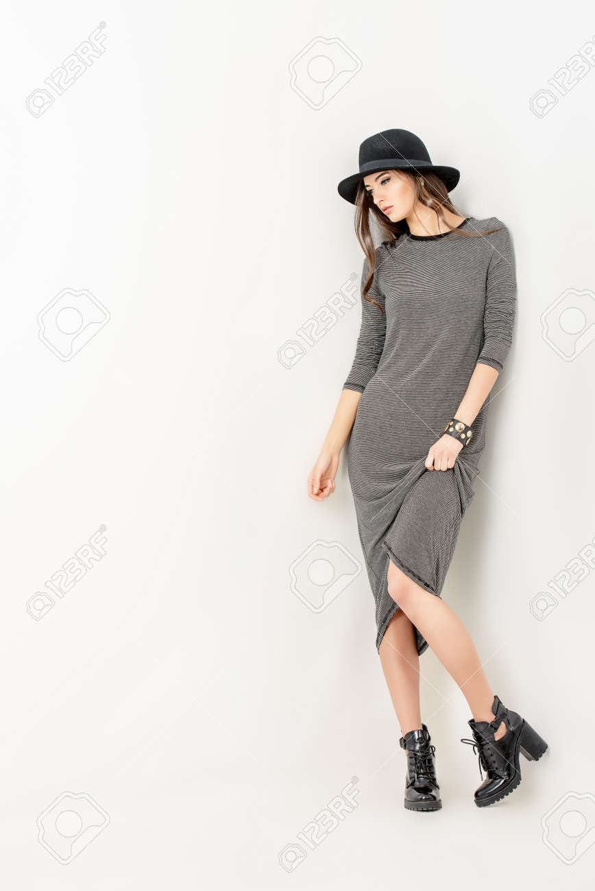 Studio shot of a magnificent young woman in a fitting dress and elegant classic hat. Stock Photo - 48266878