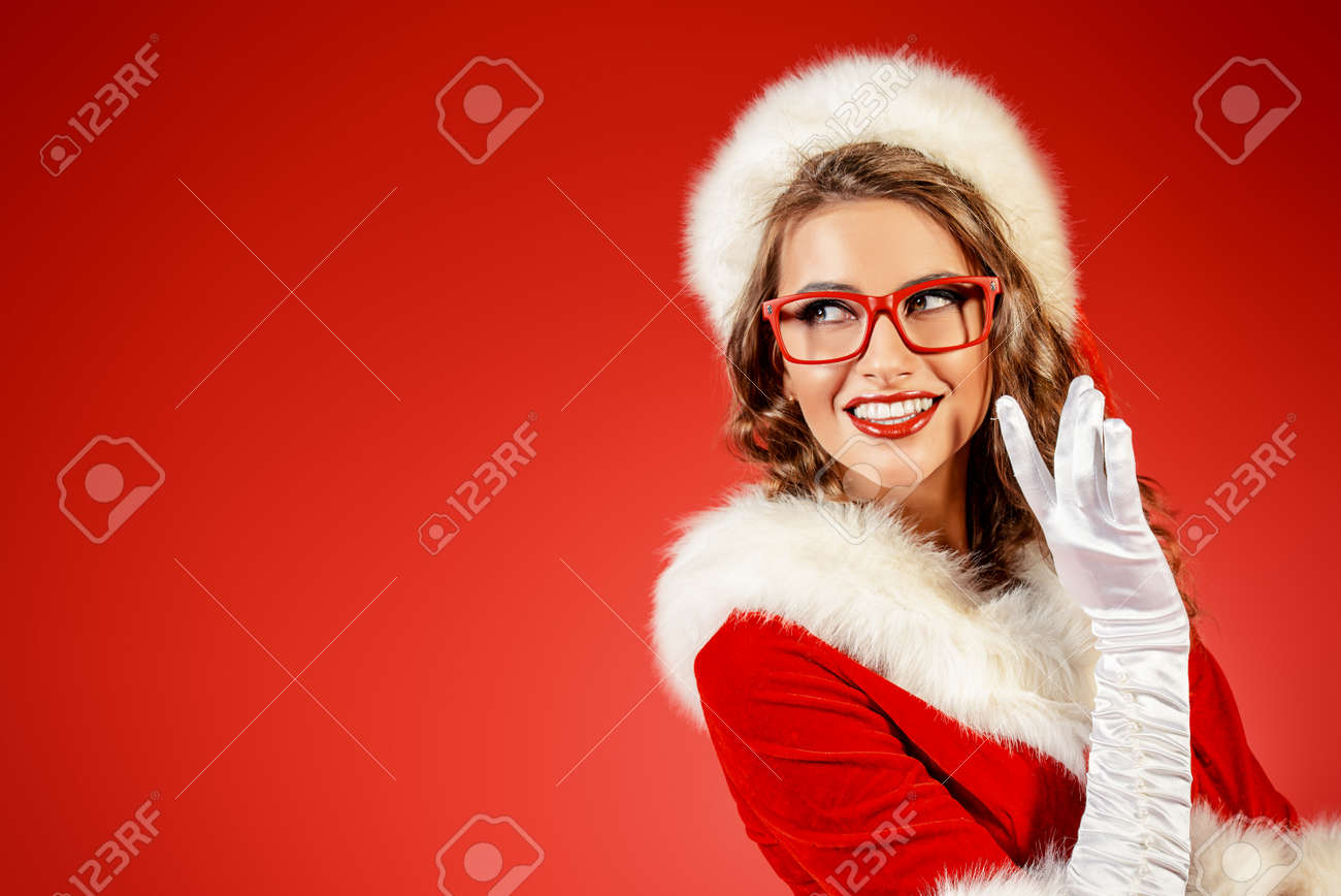 Sexy young woman in Santa Claus clothes and elegant red glasses. Red background. Christmas celebration. Stock Photo - 48704778