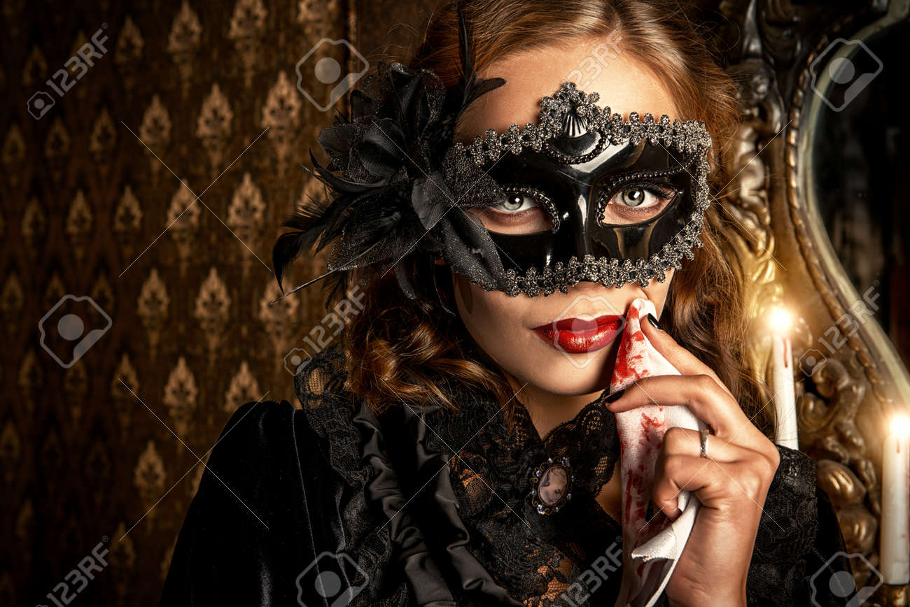 Charming mysterious girl in black mask and black medieval dress stands in a castle living room. Vampire. Halloween concept. Vintage style. - 50995790