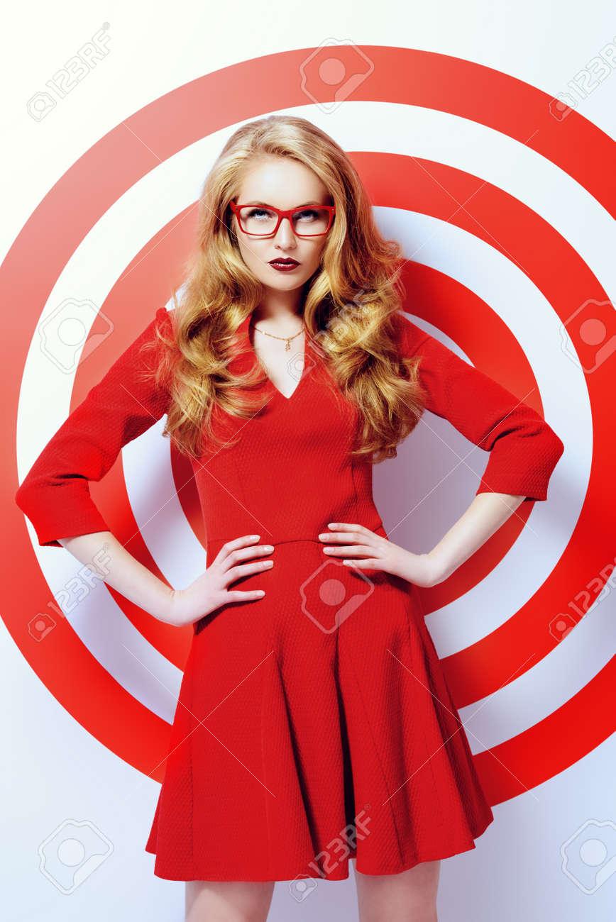 El Modelo De Manera Magnífica En Vestido Rojo Y Gafas De Color Rojo Elegante Que Presenta Sobre Los Círculos Rojos De La Meta Belleza La Moda