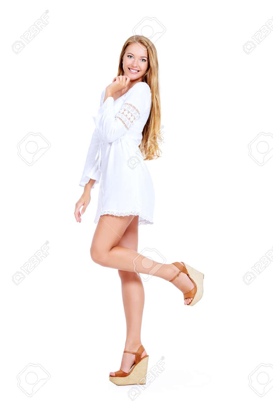 8cff87d653fab4 Aantrekkelijke jonge vrouw in een witte zomerjurk en sandalen. Geïsoleerd  dan wit. Stockfoto -