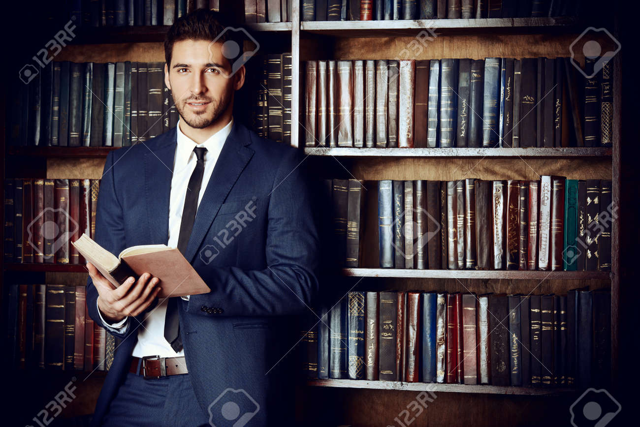 Respectable young man in the old library. Classic vintage interior. Stock Photo - 52827900