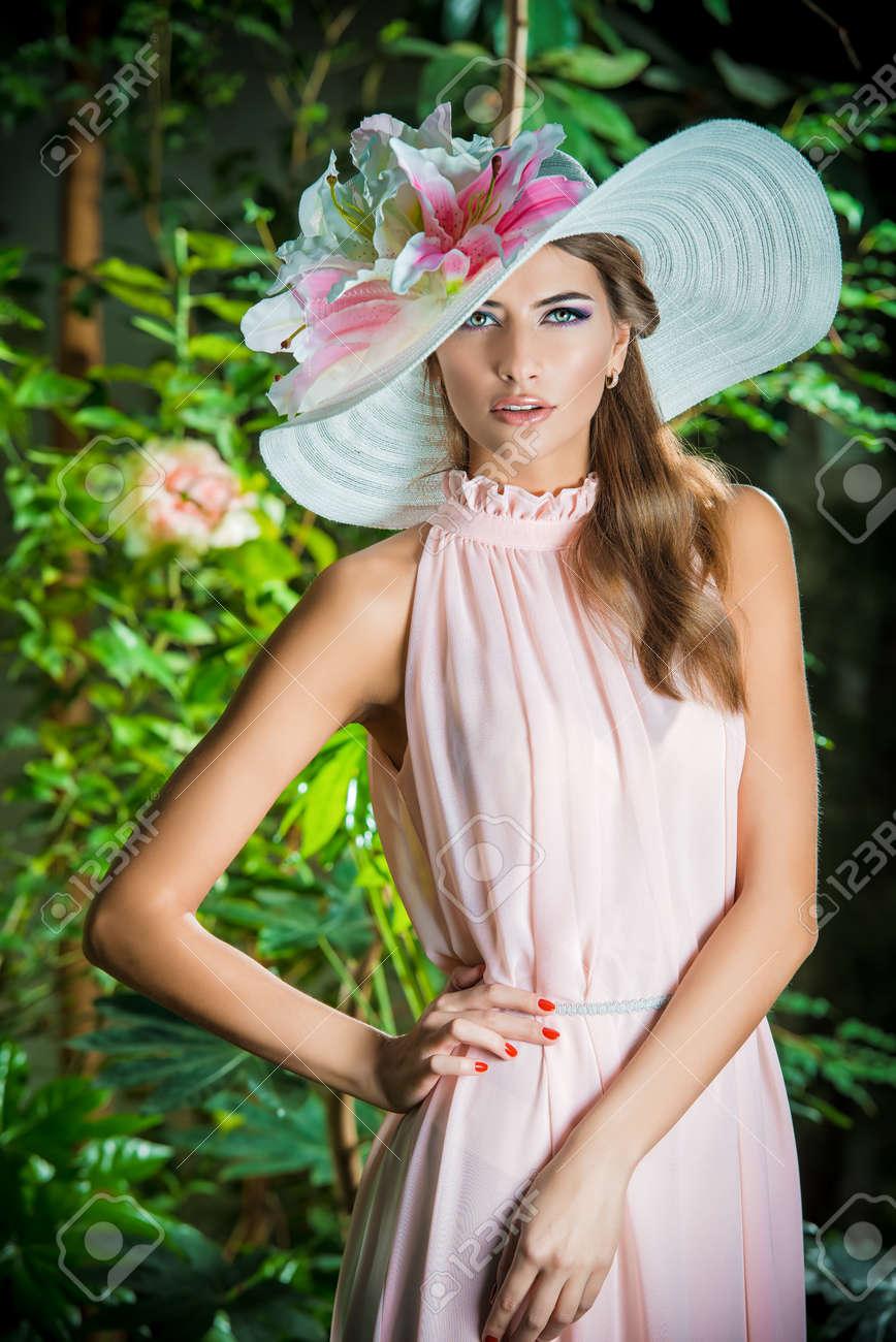 Foto de archivo - Mujer romántica hermosa en vestido ligero y elegante  sombrero que presenta en un jardín en flor. Belleza 8217ef3afff