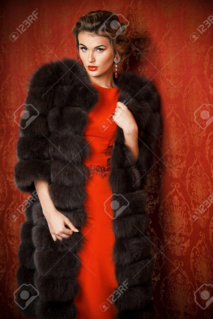 赤いドレスとビンテージ壁紙によって魅力的な豪華な毛皮のコートで