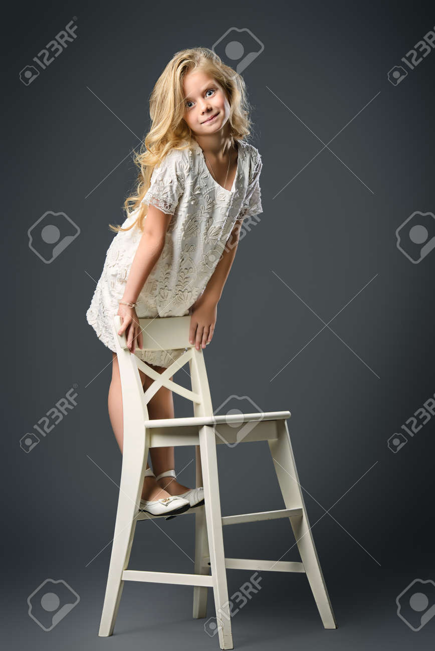 Fashion shot of a pretty little girl with beautiful blonde hair wearing  white dress. Studio 88d4c9bb1cf2