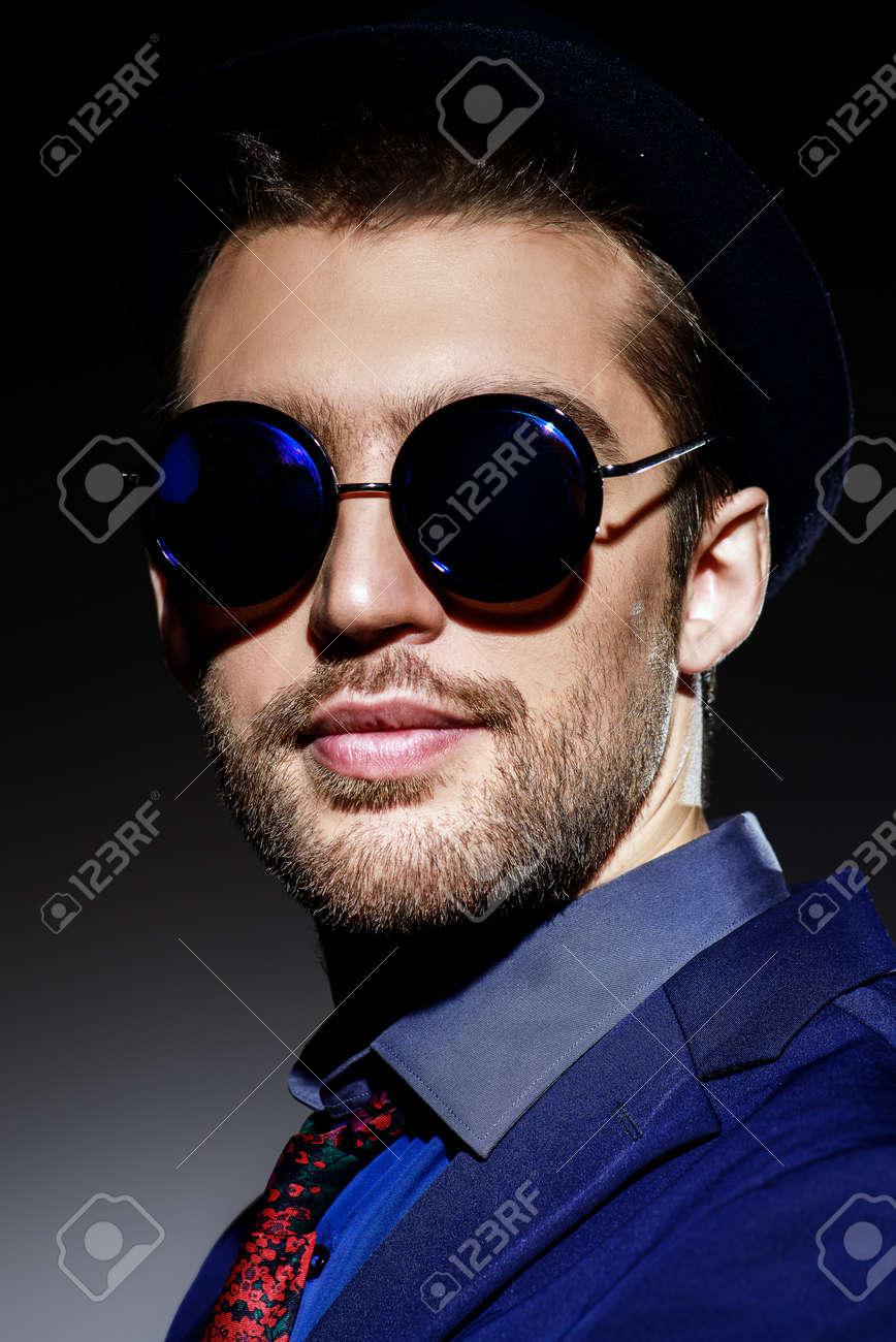39b61141262 Close-up portrait of a stylish young man wearing black round sunglasses.  Optics style