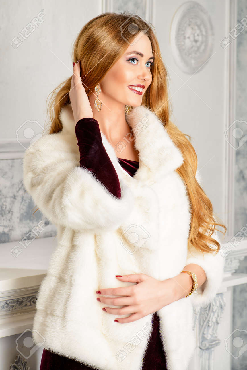 4075ca211 Elegant young woman in evening dress and mink fur jacket posing in vintage  interior. Jewellery