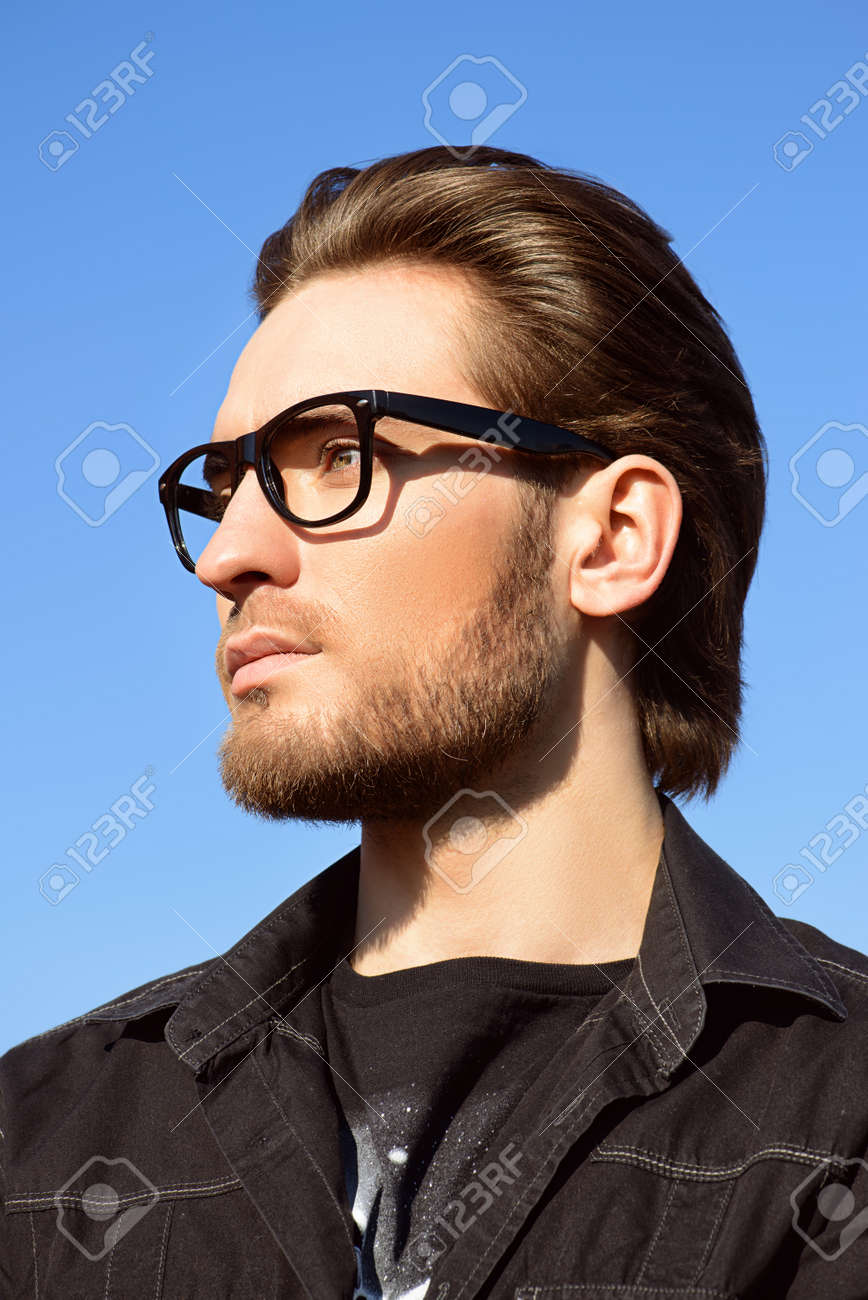 5cd9dd66249b Handsome man in black jacket and spectacles posing outdoor over blue sky.  Men's beauty,