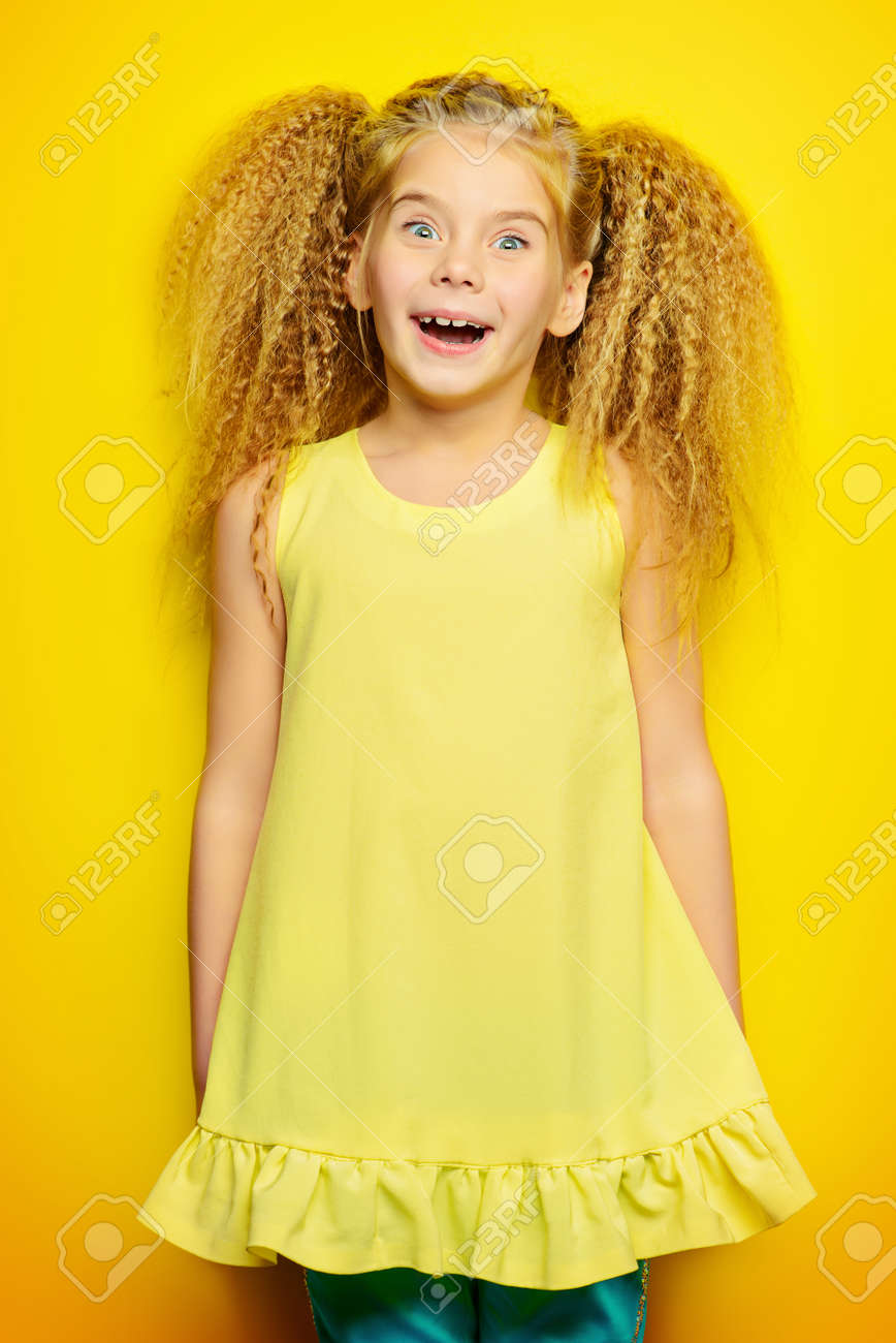 Frohes Kleines Mädchen Mit Schönen Blonden Haaren über Gelben
