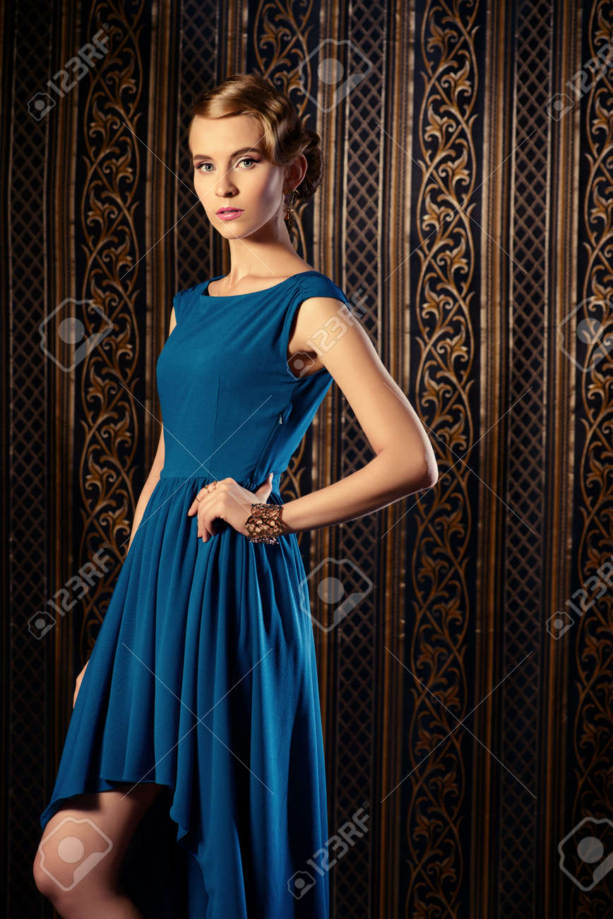 エレガントなイブニング ドレス立ってビンテージ壁紙の豪華な若い女性