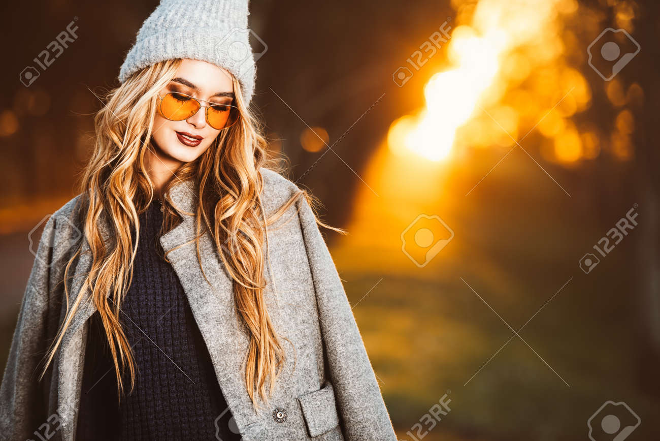 Autumn fashion. Happy young woman wearing warm sweater, a coat and a woolen hat walking in the park at a sunny autumn day. - 92295339