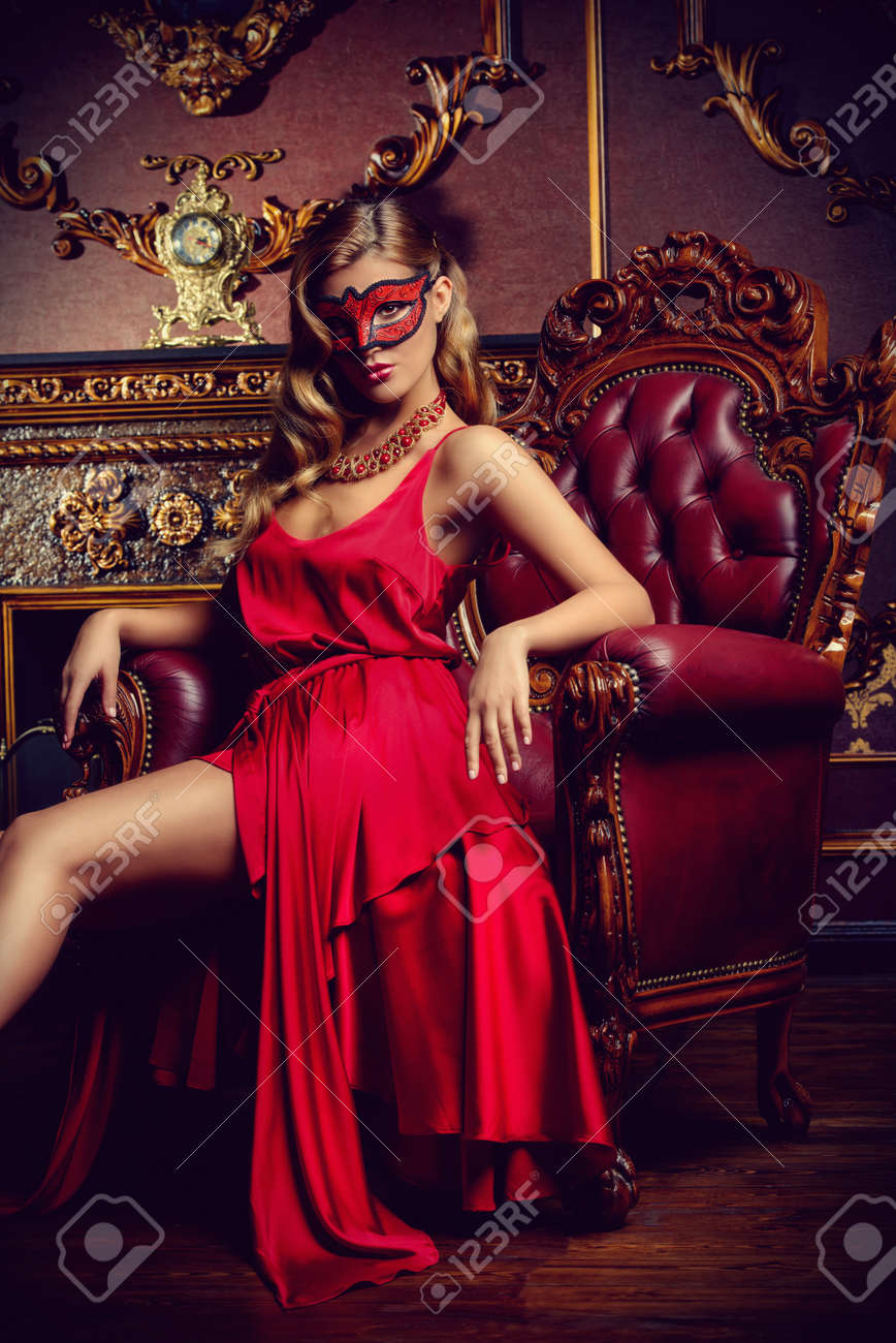 72caa11128ed Charming elegant woman in beautiful red dress and masquerade mask is  sitting in a chair in