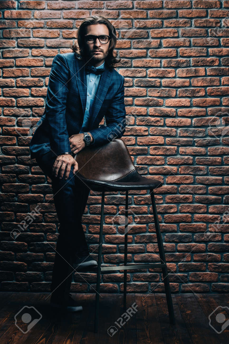 Fashion Shot Of A Handsome Man Posing By The Chair At Studio Stock Photo Picture And Royalty Free Image Image 92296757