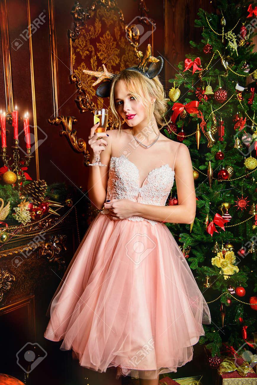 e74c10d631 Foto de archivo - Mágica noche de Navidad. Hermosa mujer en elegante vestido  de noche con una copa de vino celebra Navidad en lujosos apartamentos  decorados ...