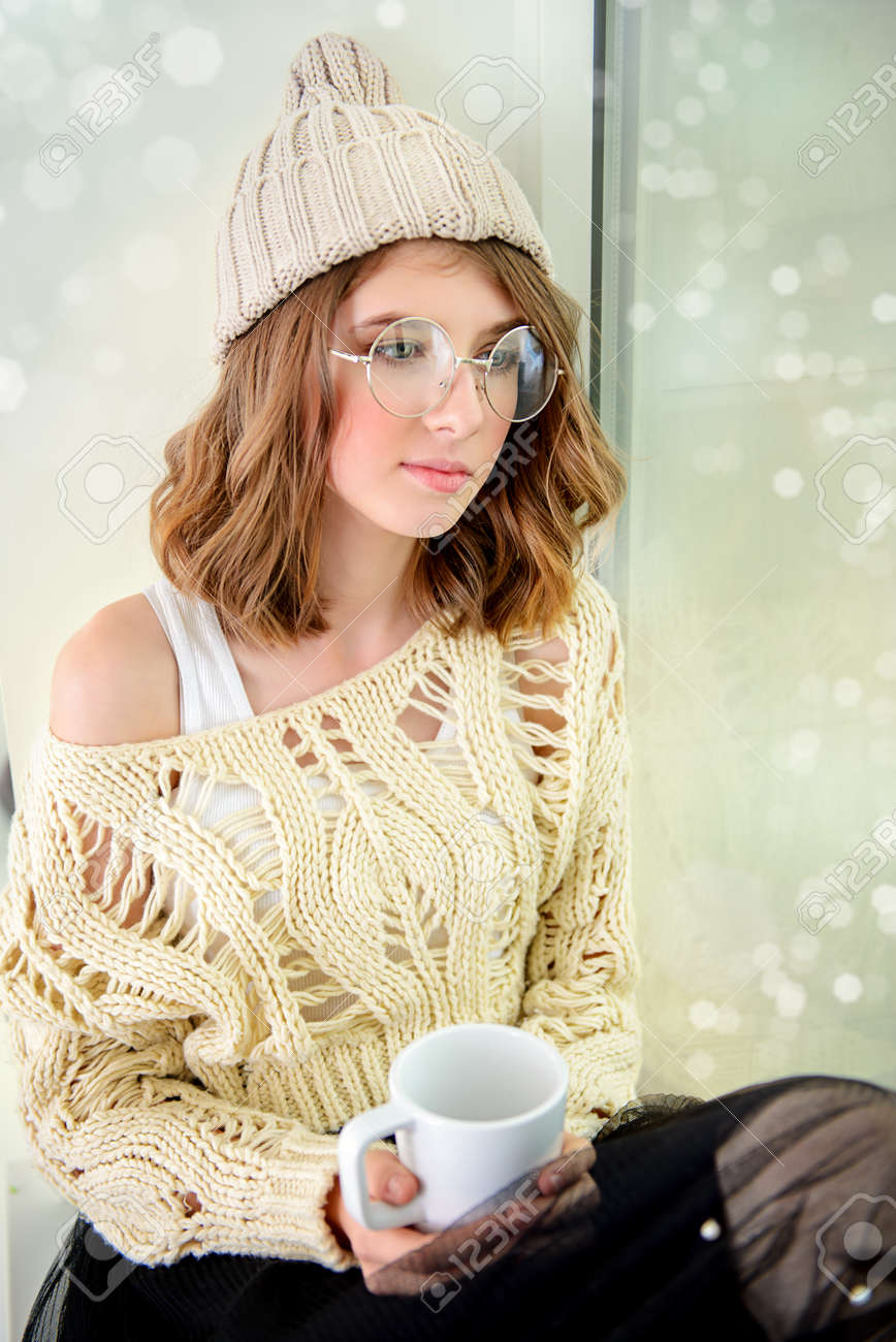 0f3057ee41e1 Pretty pensive teenage girl drinking coffee and looking to the window.  Youth style. Stock
