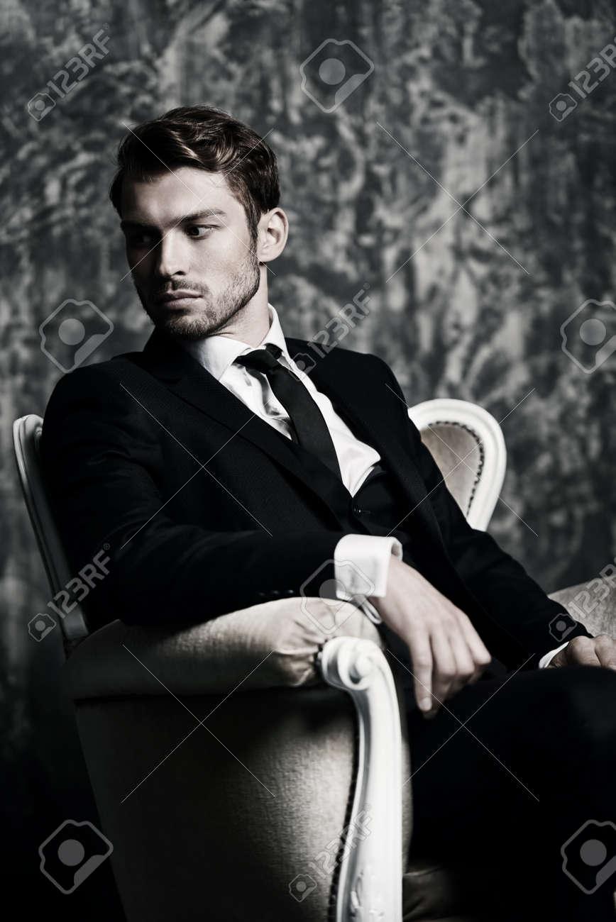 prezzo interessante enorme sconto colori armoniosi Ritratto di un uomo bello in un vestito elegante che si siede in una  poltrona su una priorità bassa del grunge. Studio girato