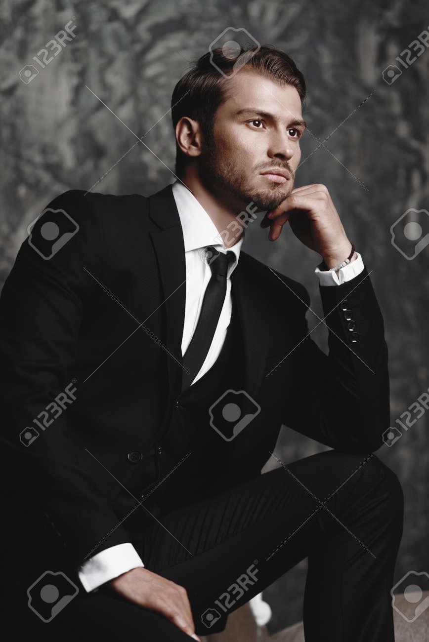 Il meglio del 2019 di modo attraente prodotti caldi Ritratto di un uomo bello in un vestito elegante su una priorità bassa del  grunge.