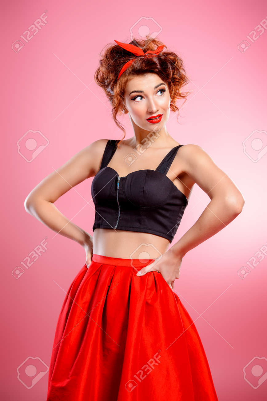 c2bb16e7578 Beautiful emotional young woman wearing skirt and top blouse poses over pink  background. Pin-