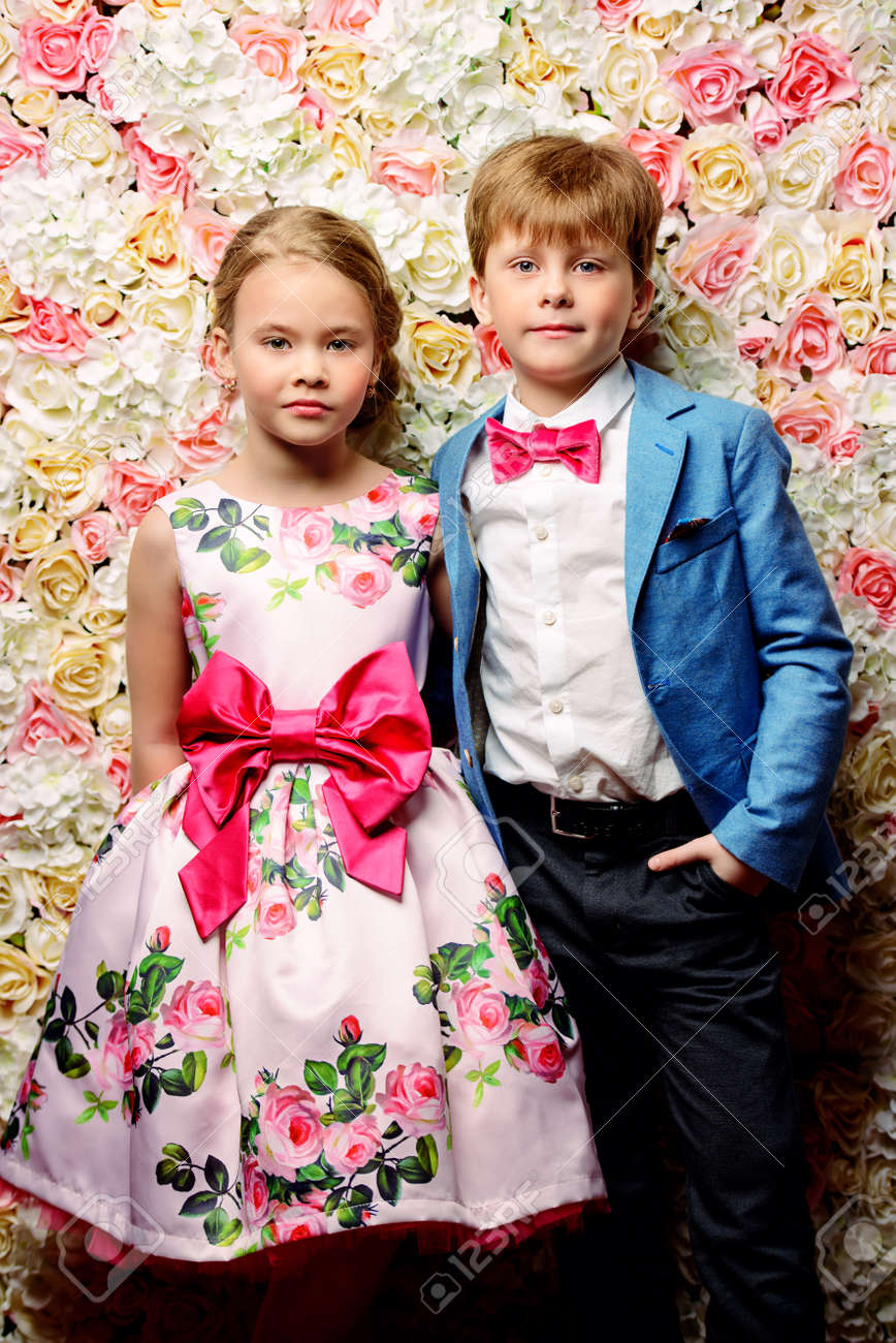 9ef467e2b38 Children s fashion. Beautiful boy and girl in elegant clothes posing on a  background of roses