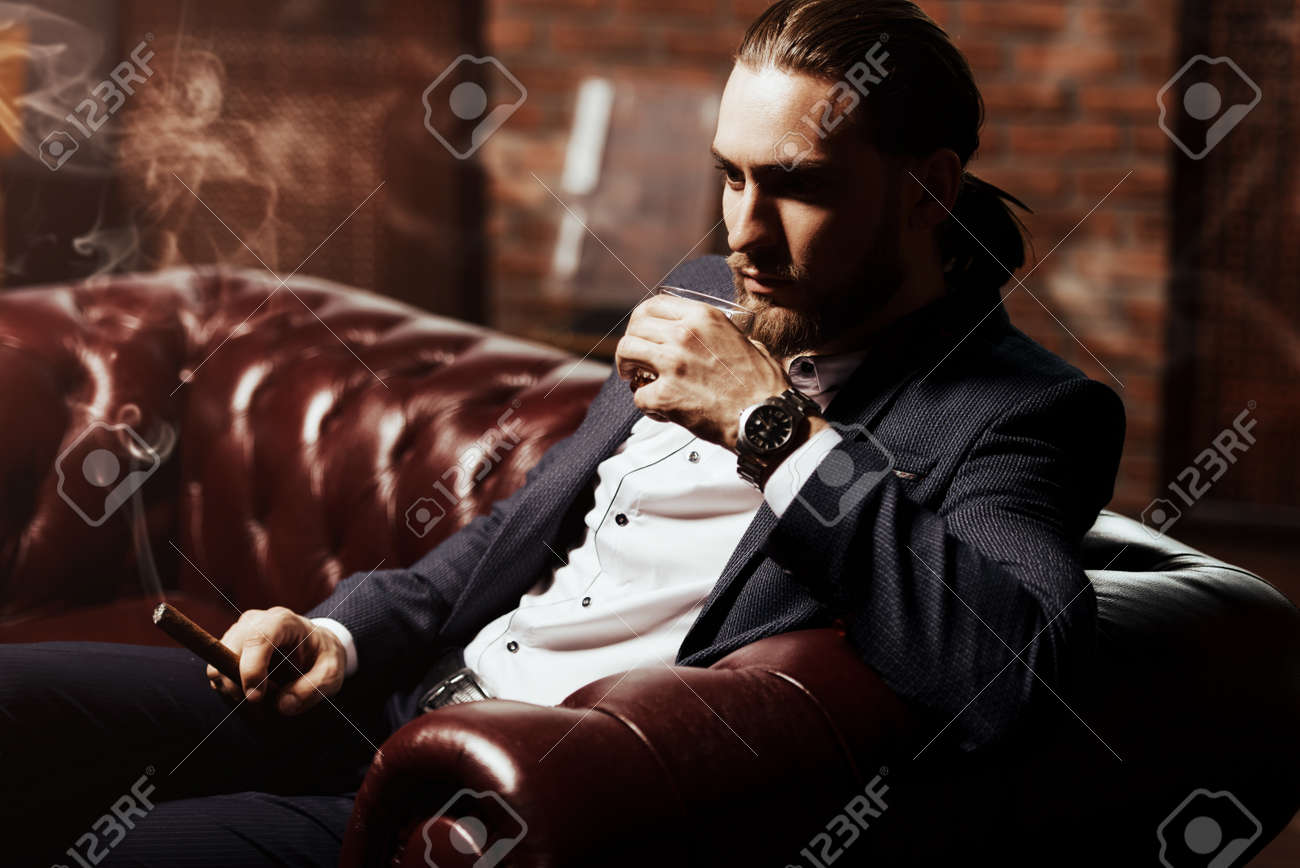 Imposing Young Man Sitting On A Leather Sofa, Drinks Whiskey And Smokes A  Cigar In