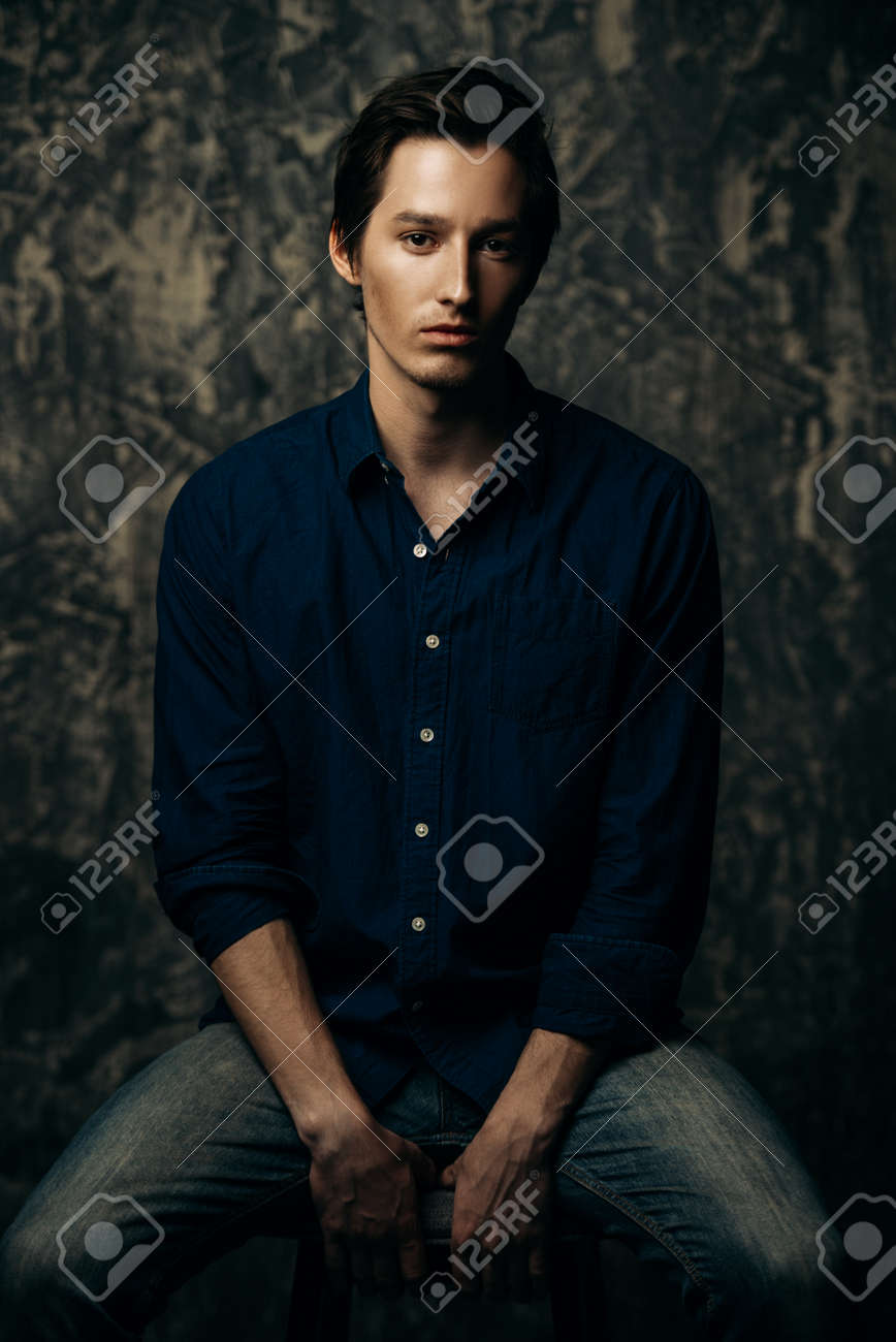 e89c0c726fb Close-up portrait of a dark-haired young man in blue shirt and jeans
