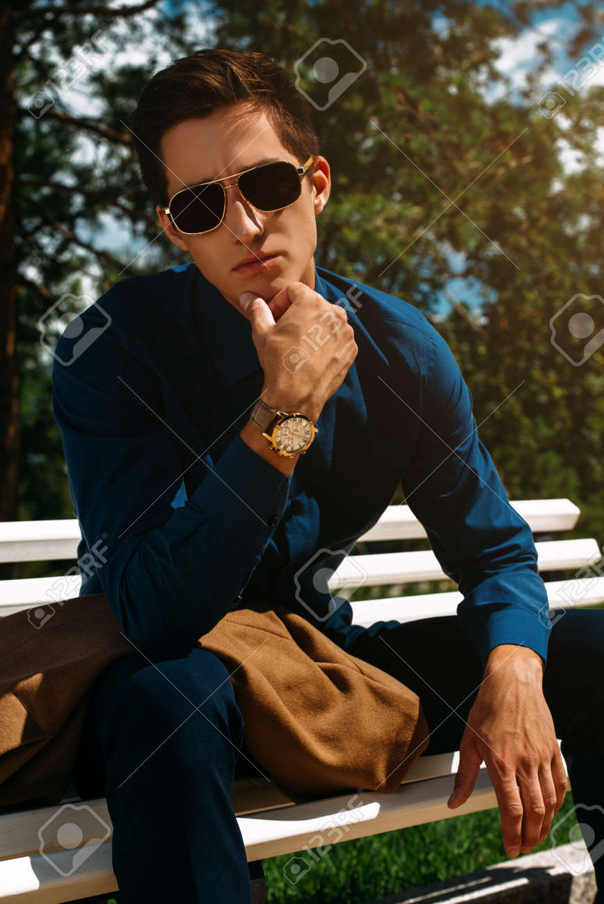 13ad9dad3c6 Portrait of a handsome young man in stylish clothes and sunglasses in a  summer park.