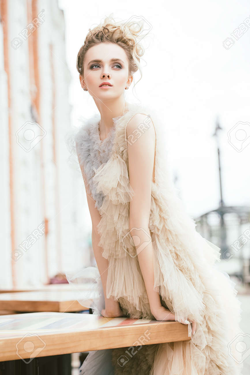 Beautiful young woman in an elegant fluffy dress posing on street. Beauty, street fashion. - 106457928