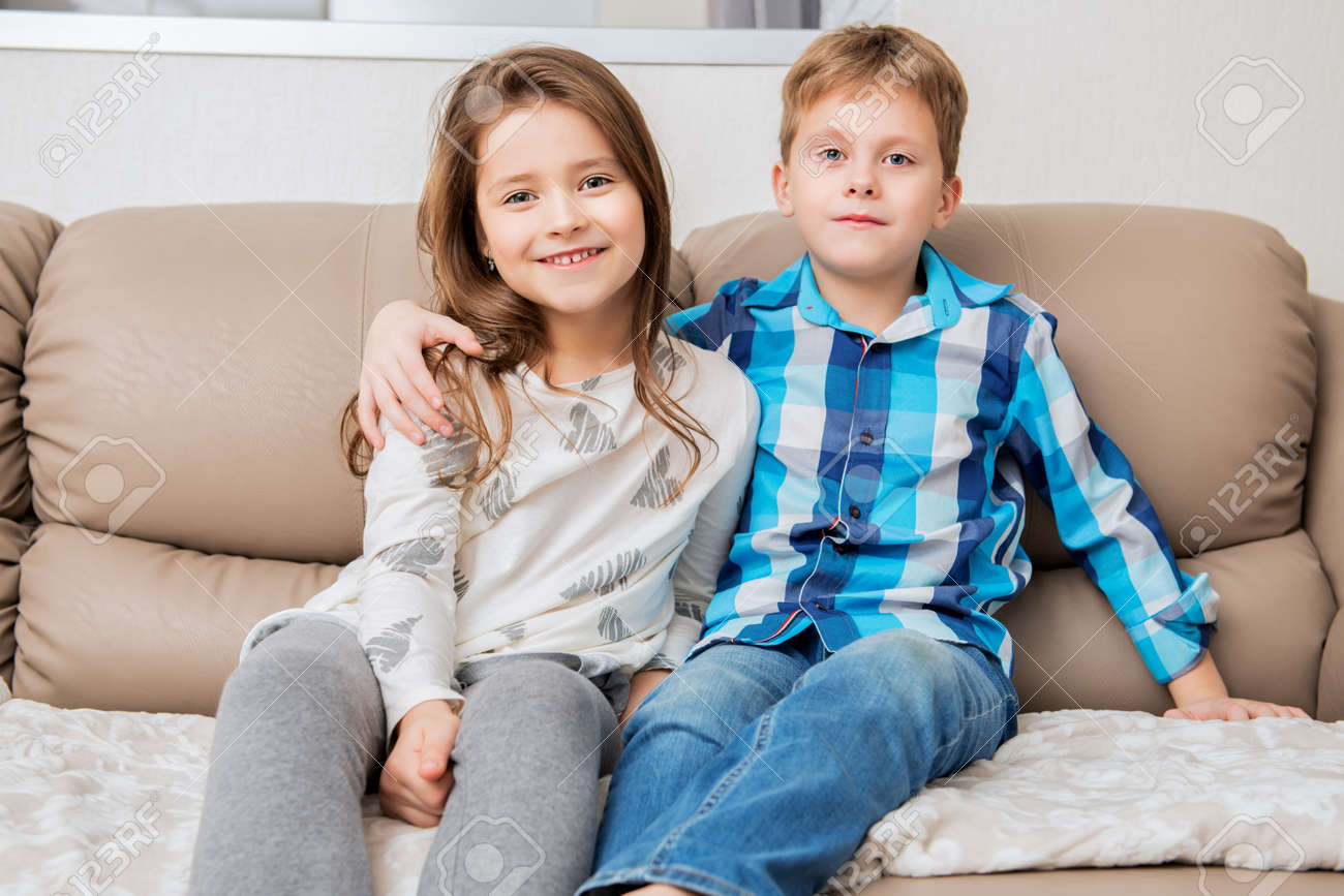 Cute boy and girl are sitting hugging on the couch. Fashion home shot. Childhood. Kid's fashion. - 115524628
