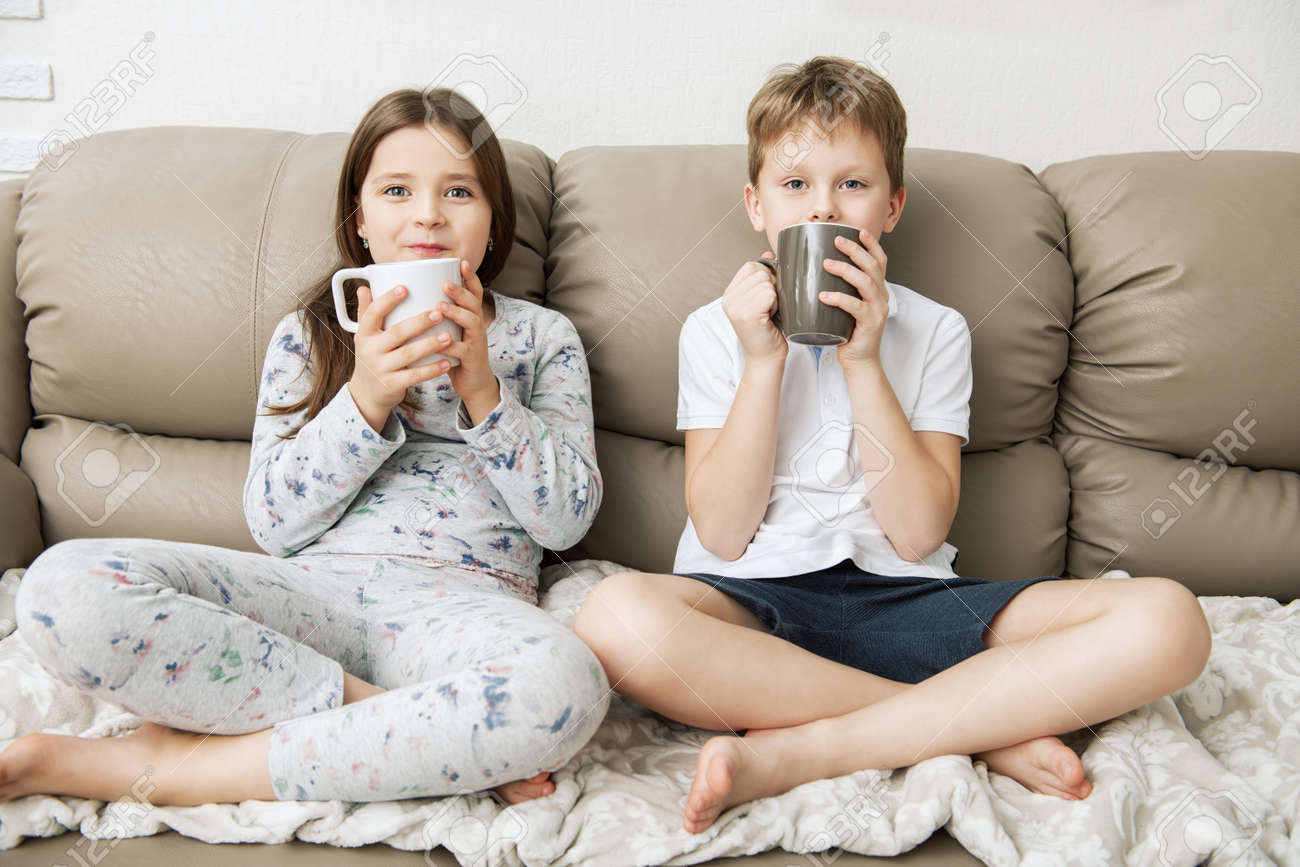 Cute boy and girl are sitting on the couch with cups. Fashion home shot. Childhood. Kid's fashion. - 117767556